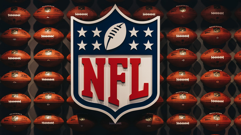The NFL logo against a backdrop of footballs