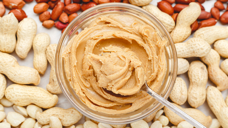A peanut butter jar and different types of peanuts