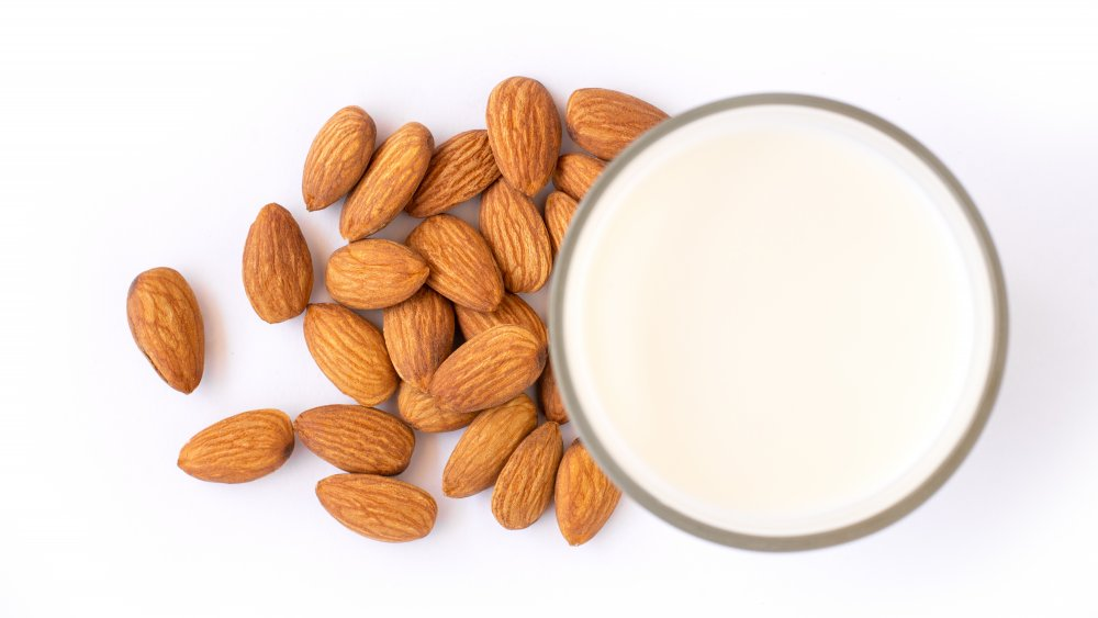a cup of almond milk next to almonds