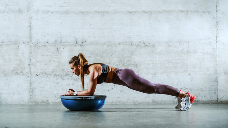 A woman doing planks with a BOSU ball