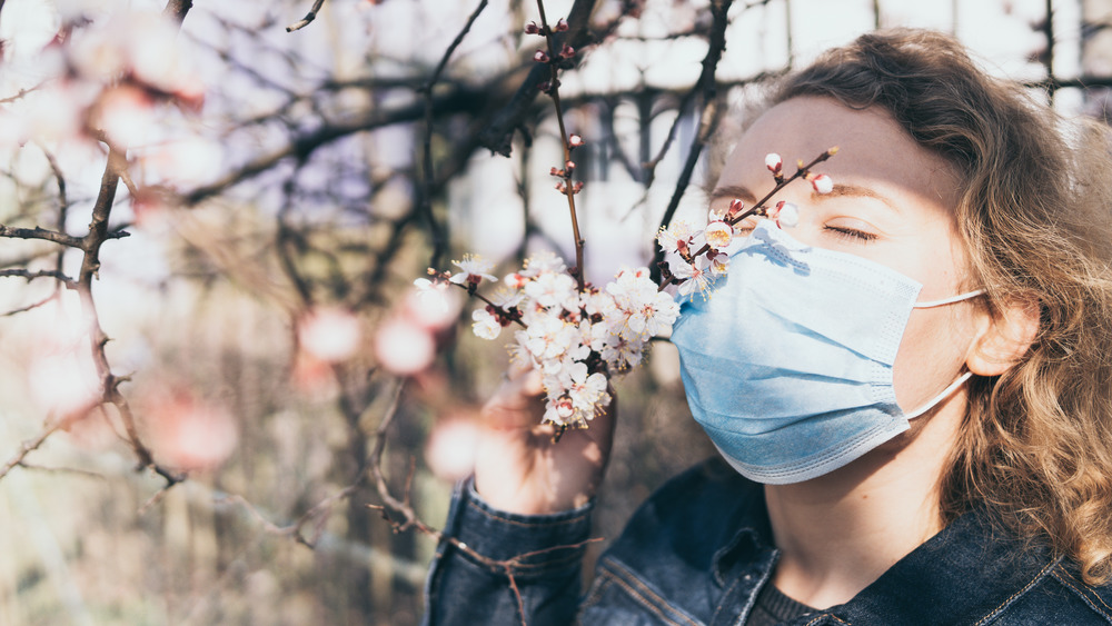 Woman wearing a face mask sniffs tree blossoms