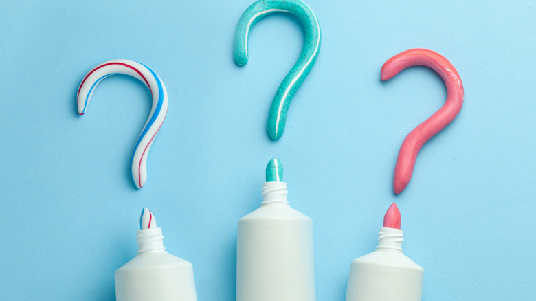 Three question marks above three tubes of toothpaste