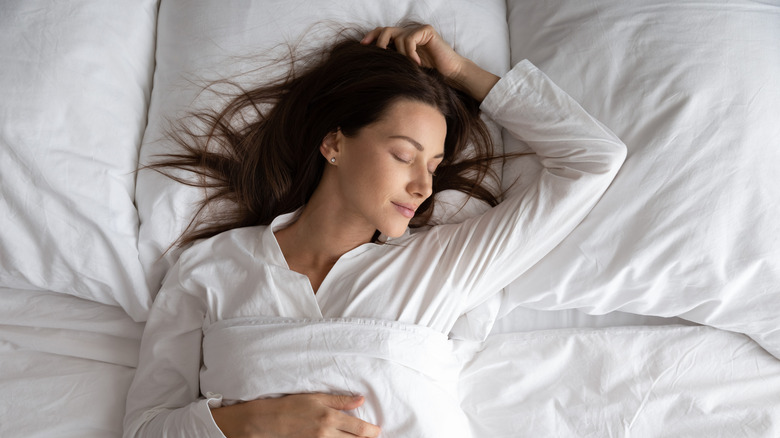 woman sleeping soundly in white sheets and pajamas