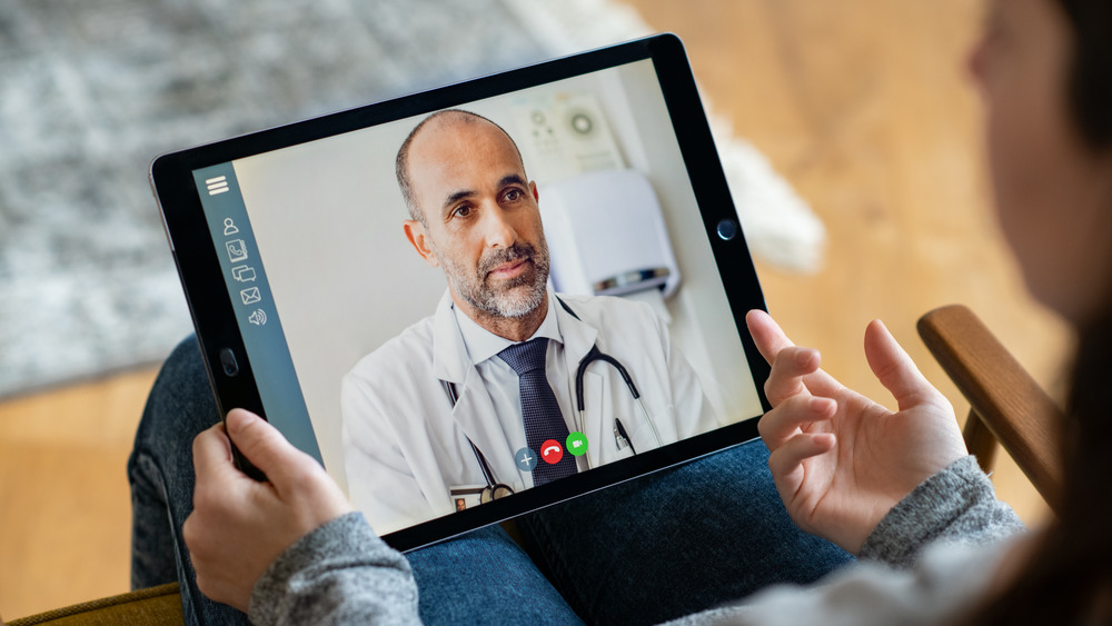 Patient holding an iPad with doctor on a virtual call