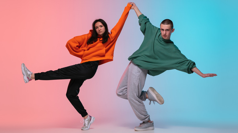 young couple dressed in loose clothing striking a dance pose