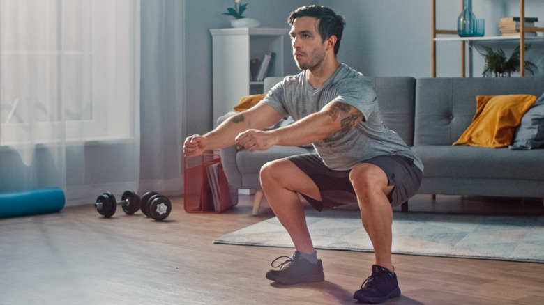 Man performing a squat in his home