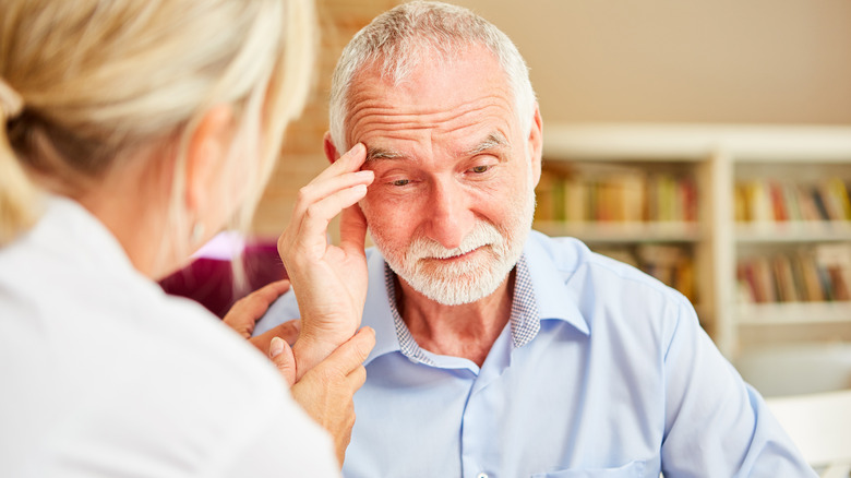 A caretaker talking to an elderly man while he touches his head