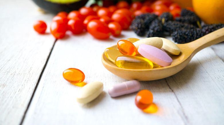 spoonful of vitamins with fruits and vegetables in background