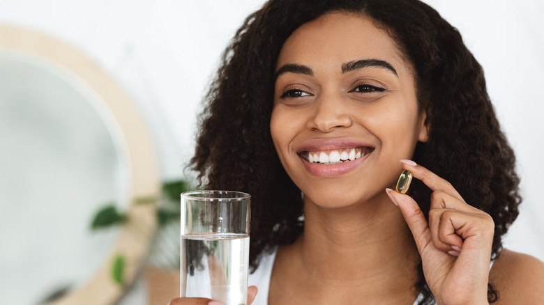 Woman holding glass of water and fish oil supplement