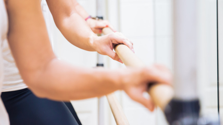People working out with their hands on a ballet barre