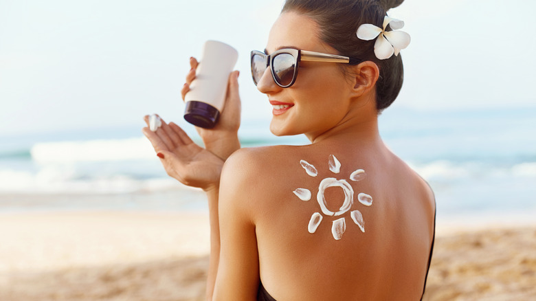 Woman applying sunblock while at the beach