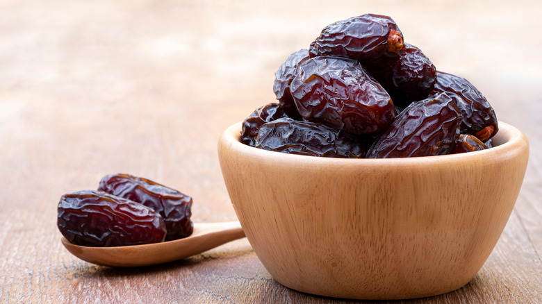 A wooden bowl full of dates