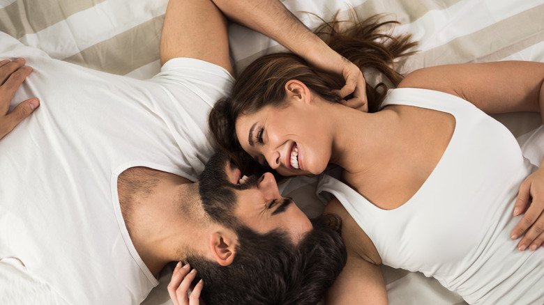 photo of woman and man in bed smiling