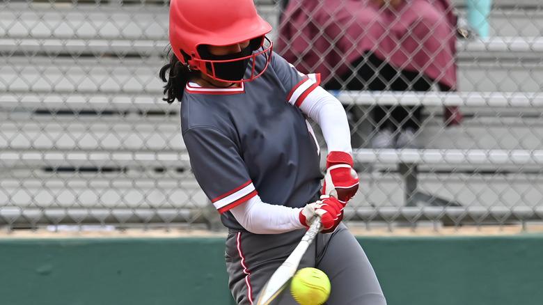 A softball player hitting the ball