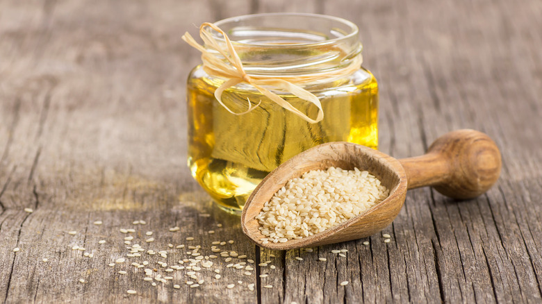 glass jar of sesame oil and a scoop of raw sesame seeds in front