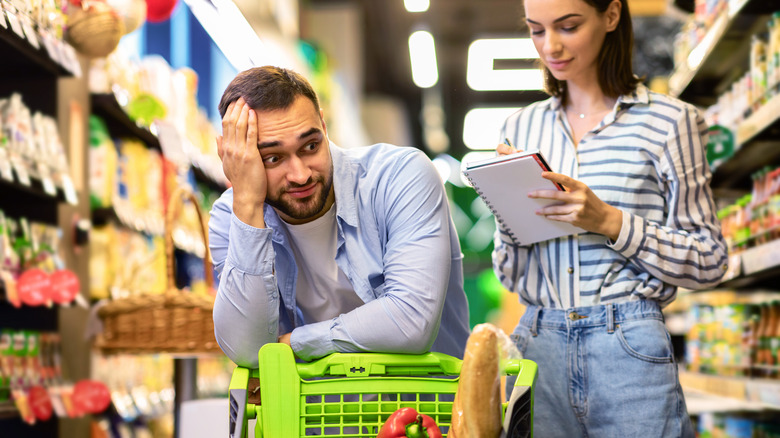 Couple going through shopping list while in grocery store