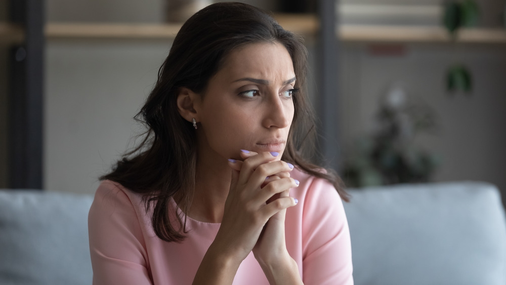 Person sitting with fingers intertwined looking off into the distance