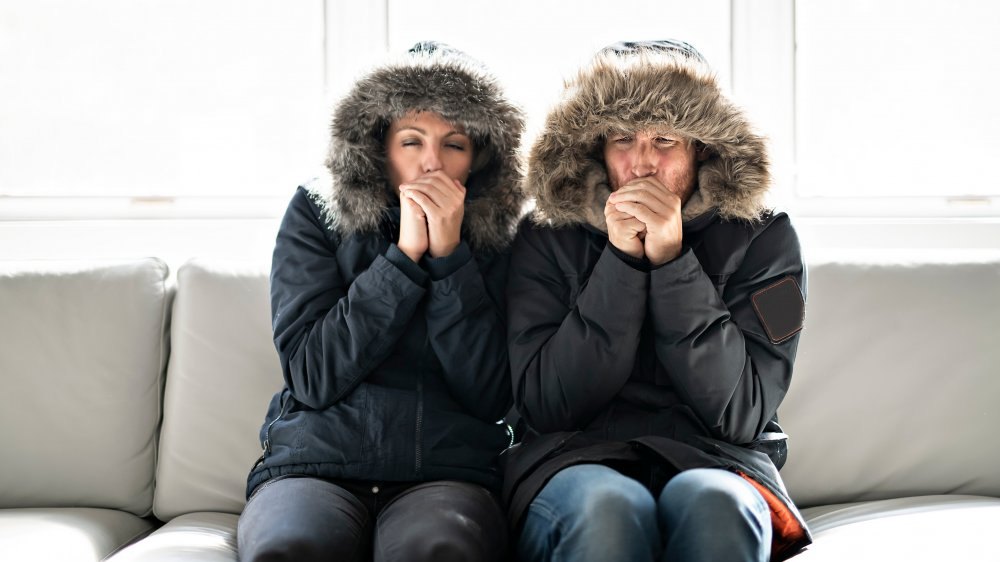 Couple bundled in winter coats on sofa and coughing