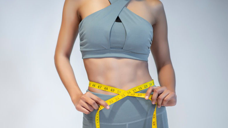 Close-up of a woman measuring her waist after exercise