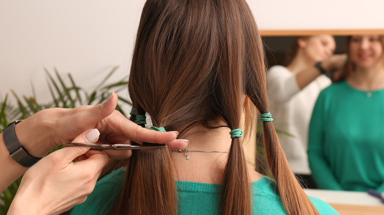 Hands holding scissors cutting a woman's hair for donation