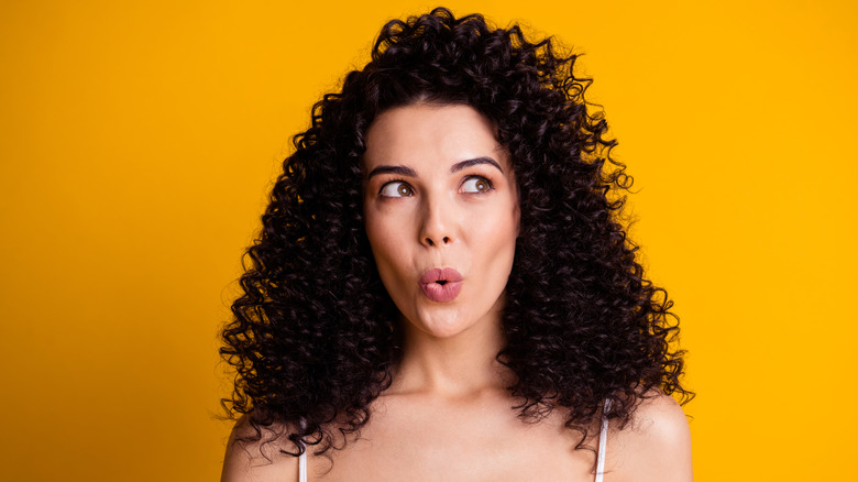 Woman trying to whistle on a orange background