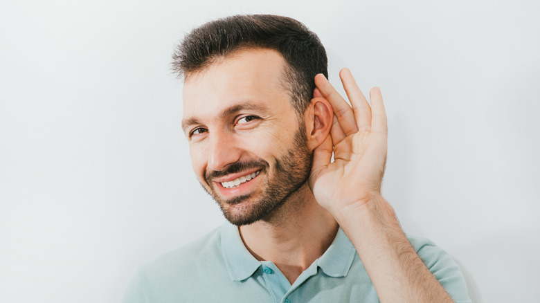 A smiling man cupping his ear