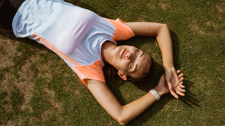woman laying on the grass in workout clothes post-workout