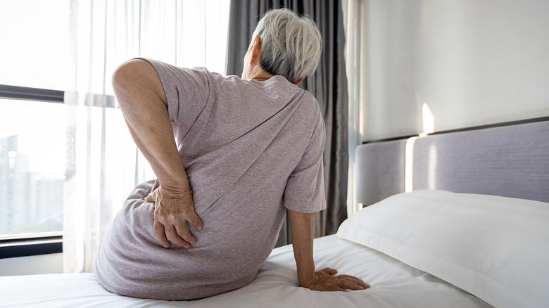 Elderly woman waking up and holding back