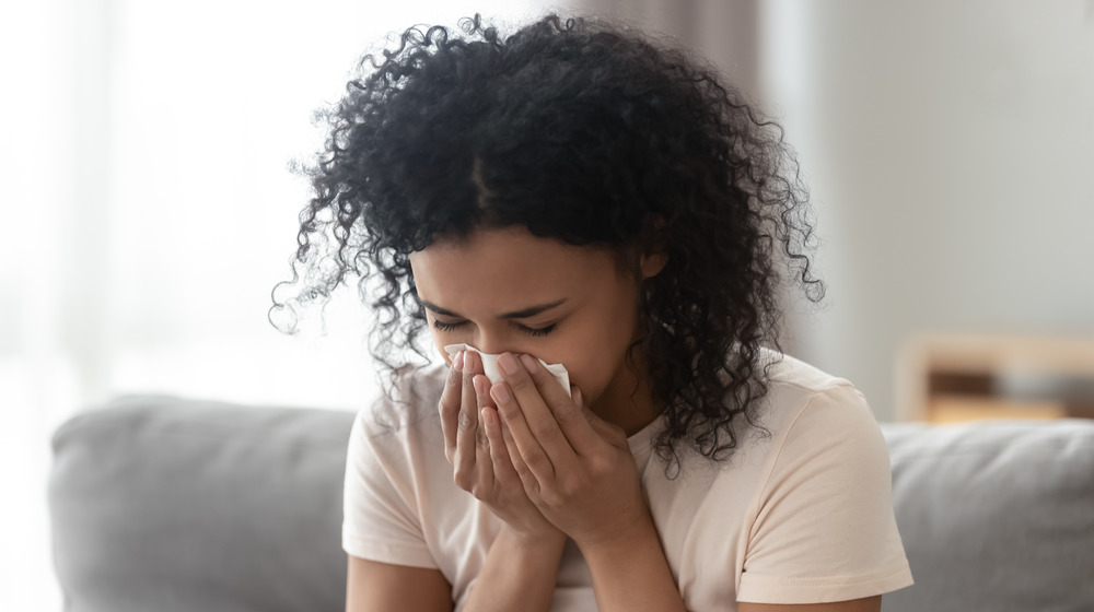 Woman sitting on the couch and blowing her nose