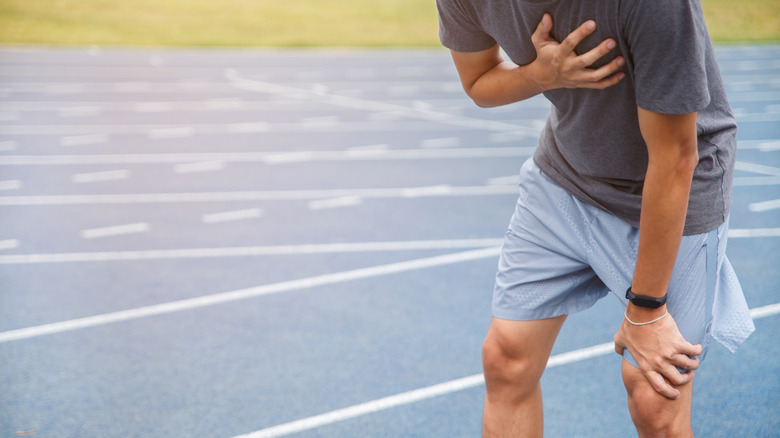 Man holding chest while running