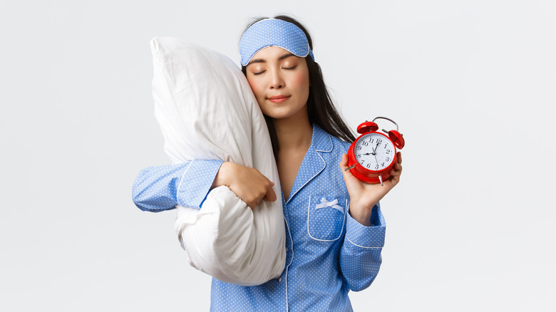Woman in blue pajamas and sleeping mask, holding pillow and alarm clock with eyes closed