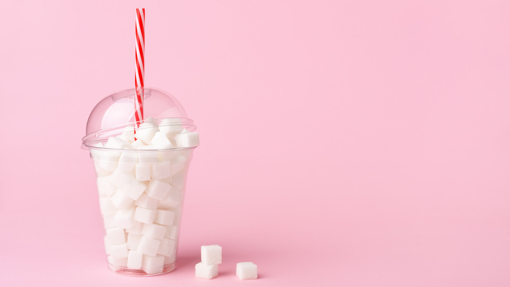 A plastic cup filled with sugar cubes with a pink background