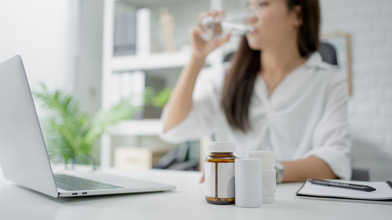 A woman drinks water next to several pill bottles