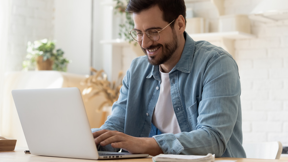 Man in glasses typing on computer