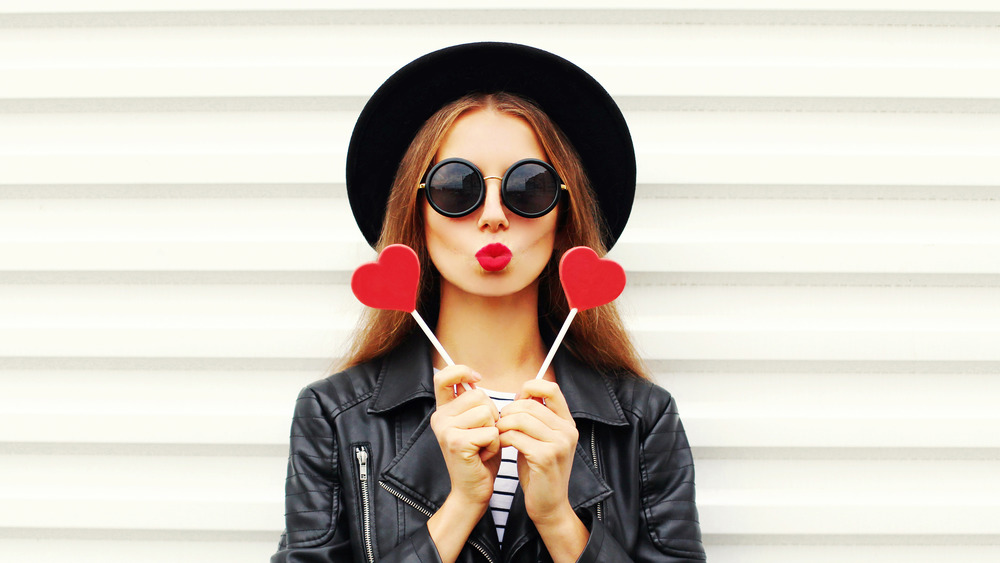 Woman holding up two hearts next two her heart shaped lips