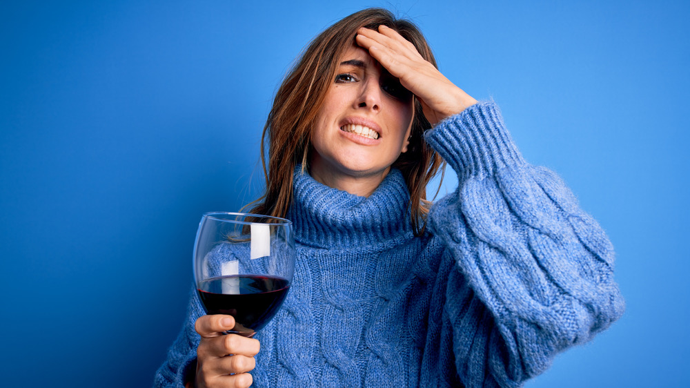 Person in blue sweater grimacing and holding glass of red wine with hand on head