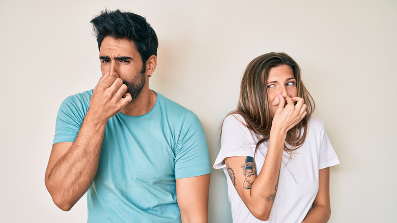Man and woman holding their noses over smell