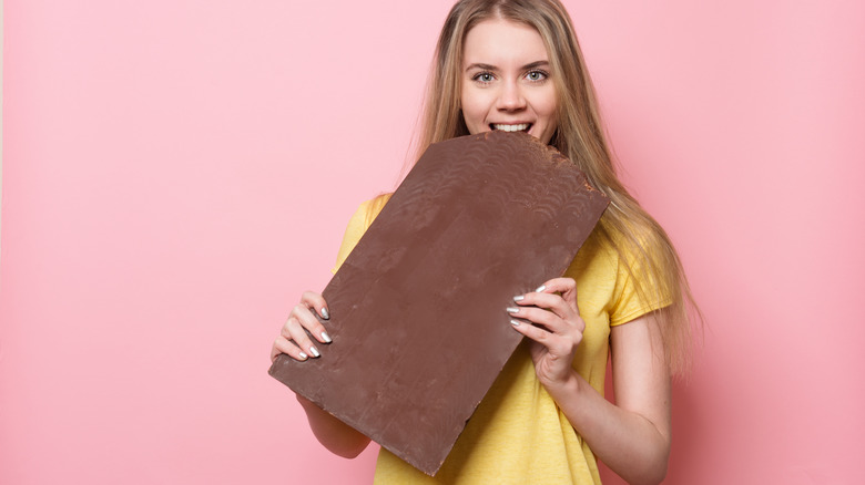 Woman holding and eating giant chocolate bar