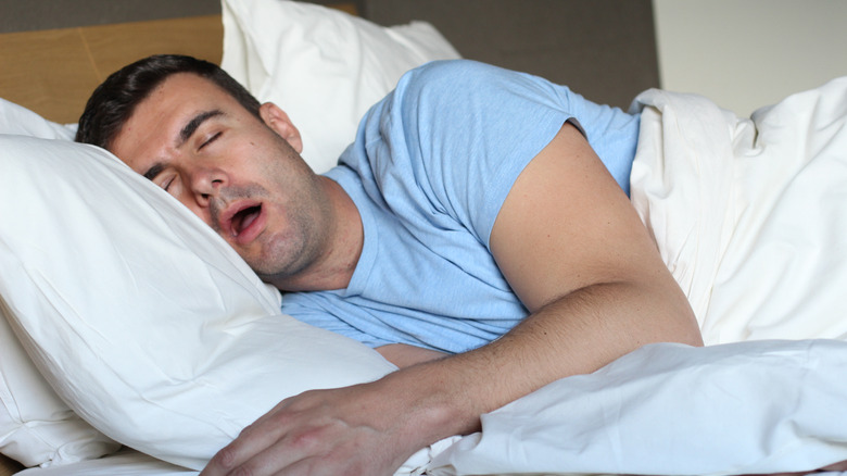 a middle aged man drooling while sleeping in bed