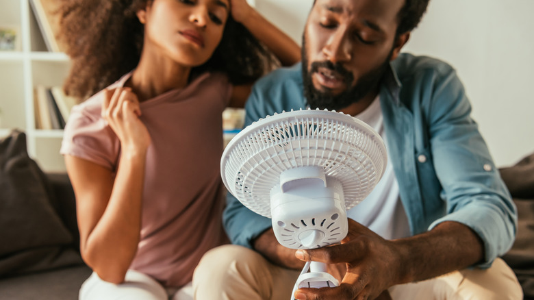 Overheated couple with handheld fan