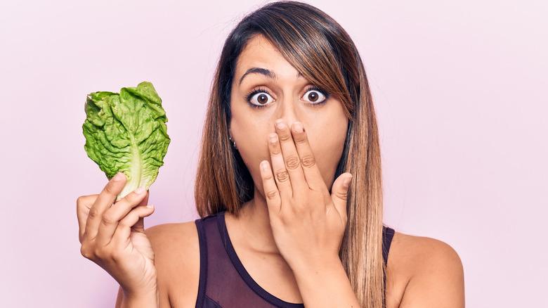 woman holding lettuce leaf