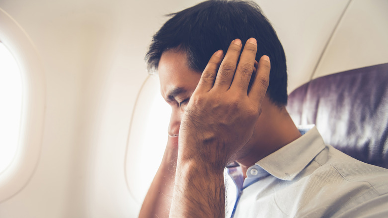 A man holding his ears in pain while on a plane