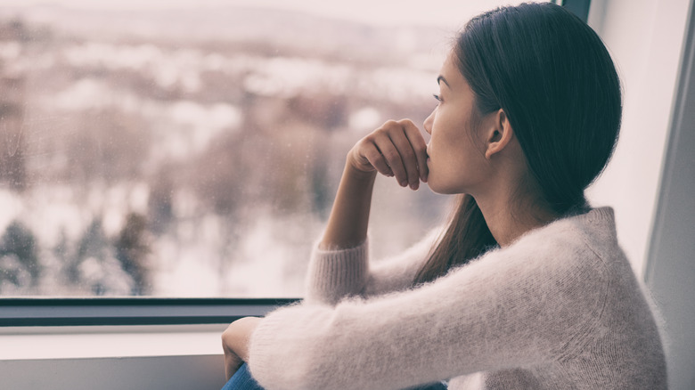 pensive woman staring out her window