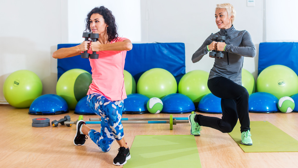 Two women holding hand weights and performing curtsy lunges