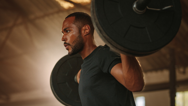 A man lifts a heavy barbell