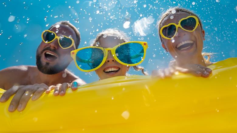 Three people having fun in a pool