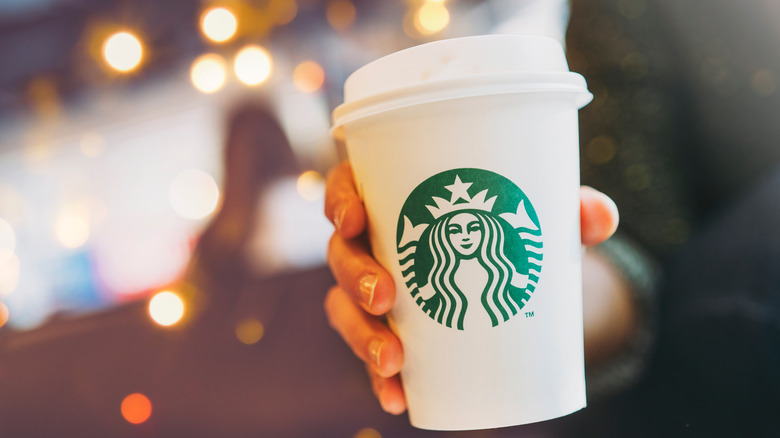 Woman's hand holding Starbucks cup