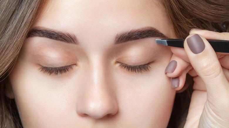 Plucking eyebrows with tweezers