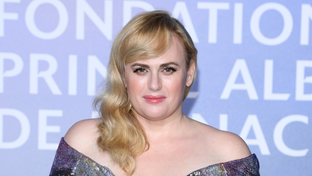 Rebel Wilson grinning in an off the shoulder gown