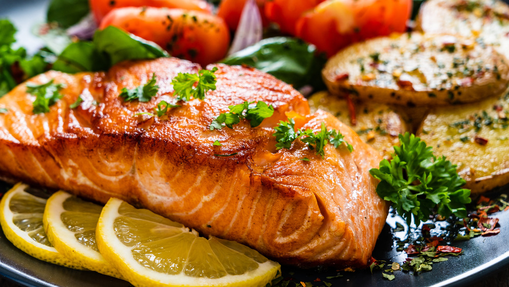 Salmon cooked with vegetables, lemon and herbs.